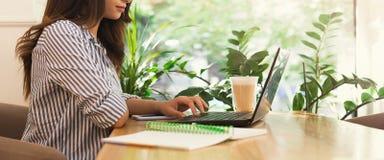 Νέα γυναίκα χρησιμοποιώντας το lap-top στον καφέ και πίνοντας τον καφέ στοκ εικόνες
