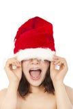Νέα γυναίκα Χριστουγέννων που χρησιμοποιεί το santa ΚΑΠ για να καλύψει τα μάτια Στοκ Εικόνα