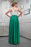 Νέα γυναίκα, όμορφο brunette σε ένα μακρύ πράσινο φόρεμα, χέρια επάνω Στοκ Φωτογραφία