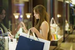 Νέα γυναίκα brunette με μερικές τσάντες αγορών στη λεωφόρο Στοκ Φωτογραφίες