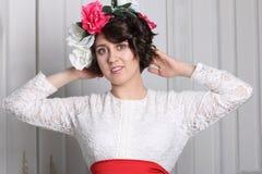 Νέα γυναίκα brunette με τη σύνθεση και το στεφάνι λουλουδιών στοκ εικόνες