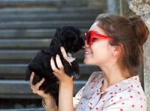 Νέα γυναίκα brunette που αγκαλιάζει το κουτάβι σκυλιών περιτυλίξεών της Στοκ Εικόνες