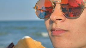 Νέα γυναίκα brunette που γλείφει τρώγοντας το παγωτό στην παραλία, το μπλε υπόβαθρο θάλασσας και τα γυαλιά ηλίου φιλμ μικρού μήκους