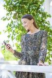 Νέα γυναίκα brunette που διαβάζει ένα μήνυμα στο τηλέφωνο στοκ εικόνα