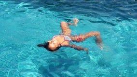 Νέα γυναίκα brunette που κολυμπά στη λίμνη που χαλαρώνει σε σε αργή κίνηση 1920x1080 φιλμ μικρού μήκους