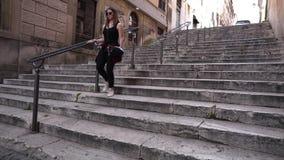 Νέα γυναίκα brunette που περπατά κάτω από τα σκαλοπάτια φιλμ μικρού μήκους