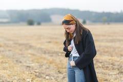 Νέα γυναίκα brunette που στέκεται στον κίτρινο τομέα φθινοπώρου στοκ φωτογραφία με δικαίωμα ελεύθερης χρήσης