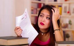 Νέα γυναίκα brunette που φορά τη ρόδινη τοπ συνεδρίαση από το γραφείο με το σωρό των βιβλίων που τοποθετούνται σε το, στηργμένος  Στοκ Φωτογραφίες