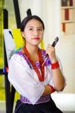 Νέα γυναίκα brunette που φορά τον παραδοσιακό των Άνδεων ιματισμό, που κρατά ψηλά τη βούρτσα χρωμάτων και που θέτει, καμβάς πίσω, Στοκ Φωτογραφίες