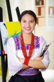 Νέα γυναίκα brunette που φορά τον παραδοσιακό των Άνδεων ιματισμό, τις βούρτσες χρωμάτων εκμετάλλευσης και την τοποθέτηση, καμβάς Στοκ φωτογραφίες με δικαίωμα ελεύθερης χρήσης