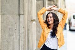 Νέα γυναίκα brunette που χαμογελά στο αστικό υπόβαθρο Στοκ Φωτογραφία