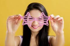 Νέα γυναίκα brunette στη ρόδινη κορυφή δεξαμενών στο κίτρινο υπόβαθρο αστείο κορίτσι με τα ρόδινα γυαλιά ηλίου Εστίαση στα γυαλιά Στοκ Εικόνα