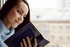 Νέα γυναίκα brunette στο μπλε μάλλινο πουλόβερ, που διαβάζει ένα ενδιαφέρον βιβλίο στο windowsill στο δωμάτιο στη βροχή, νεφελώδη Στοκ φωτογραφία με δικαίωμα ελεύθερης χρήσης