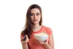 Νέα γυναίκα brunette Cutie με τη TV μακρινή και pop-corn στα χέρια Στοκ εικόνες με δικαίωμα ελεύθερης χρήσης