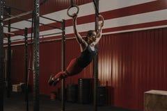 Νέα γυναίκα crossfit που ταλαντεύεται στα γυμναστικά δαχτυλίδια στοκ εικόνα
