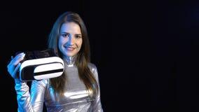 Νέα γυναίκα Cyber στον ασημένιο ιματισμό που παρουσιάζει εικονική πραγματικότητα googles απόθεμα βίντεο