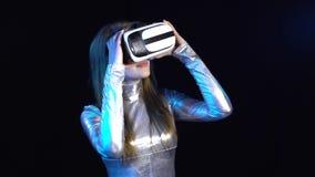 Νέα γυναίκα Cyber στον ασημένιο ιματισμό που φορά την εικονική πραγματικότητα googles φιλμ μικρού μήκους