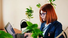 Νέα γυναίκα eyeglasses που δακτυλογραφεί το κείμενο στο lap-top στην αρχή απόθεμα βίντεο