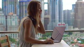 Νέα γυναίκα freelancer workes στο lap-top της που έχει μια συνομιλία σε ένα τηλέφωνο κυττάρων σε ένα μπαλκόνι με ένα υπόβαθρο του φιλμ μικρού μήκους