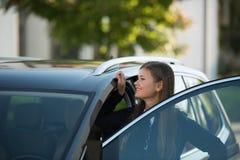 Νέα γυναίκα gats στο αυτοκίνητο στοκ εικόνες