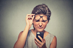 Νέα γυναίκα Headshot με τα γυαλιά που έχουν το πρόβλημα που βλέπει το τηλέφωνο κυττάρων Στοκ Φωτογραφίες