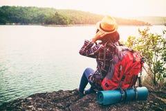 Νέα γυναίκα hipster με τη συνεδρίαση backpacker στην απόλαυση πετρών στοκ φωτογραφίες