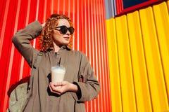 Νέα γυναίκα Hipster με το σγουρό κόκκινο καφέ κατανάλωσης τρίχας ενάντια στον κόκκινο και κίτρινο τοίχο Τουρίστας με την κατάψυξη Στοκ φωτογραφία με δικαίωμα ελεύθερης χρήσης