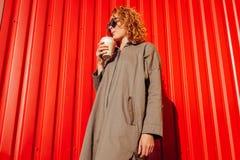 Νέα γυναίκα Hipster με το σγουρό κόκκινο καφέ κατανάλωσης τρίχας ενάντια στον κόκκινο τοίχο Μοντέρνος σπουδαστής που περιμένει το Στοκ Φωτογραφίες