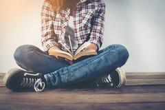 Νέα γυναίκα hipster που κρατά την ανοικτή συνεδρίαση βιβλίων στο ξύλινο πάτωμα Στοκ εικόνες με δικαίωμα ελεύθερης χρήσης
