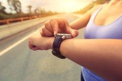 Νέα γυναίκα jogger έτοιμη να τρέξει το σύνολο και την εξέταση το αθλητικό έξυπνο ρολόι Στοκ Εικόνα