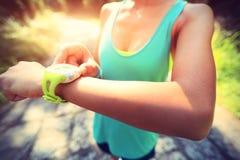 Νέα γυναίκα jogger έτοιμη να τρέξει το σύνολο και την εξέταση το αθλητικό έξυπνο ρολόι Στοκ Εικόνες