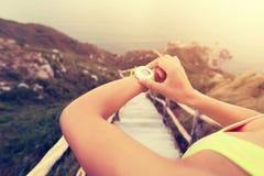 Νέα γυναίκα jogger έτοιμη να τρέξει το σύνολο και την εξέταση το αθλητικό έξυπνο ρολόι Στοκ Φωτογραφίες