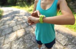 Νέα γυναίκα jogger έτοιμη να τρέξει το σύνολο και την εξέταση το αθλητικό έξυπνο ρολόι Στοκ εικόνες με δικαίωμα ελεύθερης χρήσης
