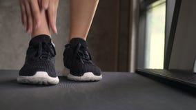 Νέα γυναίκα Jogging Treadmill στη γυμναστική και το αίσθημα του πόνου στον αστράγαλο Μπροστινή στενή επάνω άποψη φιλμ μικρού μήκους