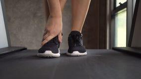 Νέα γυναίκα Jogging Treadmill στη γυμναστική και το αίσθημα του πόνου στον αστράγαλο Μπροστινή στενή επάνω άποψη απόθεμα βίντεο