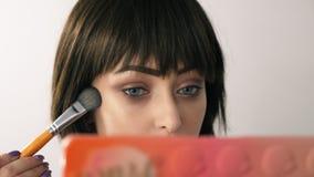Νέα γυναίκα makeup ο ίδιος μπροστά από τον καθρέφτη απόθεμα βίντεο