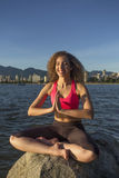 Νέα γυναίκα meditates σε έναν βράχο στον ωκεανό, χαμόγελο Στοκ εικόνες με δικαίωμα ελεύθερης χρήσης