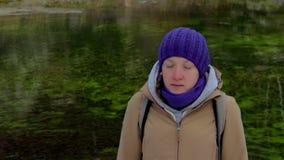 Νέα γυναίκα meditates σε ένα υπόβαθρο της πράσινης λίμνης φιλμ μικρού μήκους