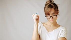Νέα γυναίκα nurd στα γυαλιά που κρατούν νευρικά τη σκέψη μανδρών κάτι απόθεμα βίντεο