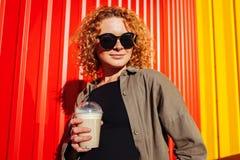 Νέα γυναίκα Prettty με το σγουρό κόκκινο καφέ εκμετάλλευσης τρίχας ενάντια στον κόκκινο τοίχο Μοντέρνο θερινό κορίτσι που χαμογελ Στοκ Φωτογραφία