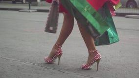 Νέα γυναίκα Shopaholic στο όμορφο φόρεμα που κρατά πολλές τσάντες αγορών περπατώντας στην οδό σε σε αργή κίνηση 1920x1080 απόθεμα βίντεο