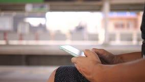 Νέα γυναίκα Texting στο κινητό τηλέφωνο και αναμονή το τραίνο στην πλατφόρμα του σταθμού μετρό μετρό 4K φιλμ μικρού μήκους