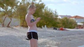 Νέα γυναικεία συνεδρίαση στην παραλία χρησιμοποιώντας την κινητή συσκευή της απόθεμα βίντεο