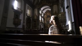 Νέα γυναικεία συνεδρίαση στον πάγκο στον καθεδρικό ναό φιλμ μικρού μήκους