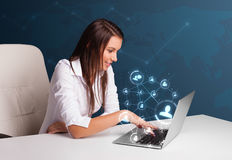 Νέα γυναικεία συνεδρίαση στο γραφείο και δακτυλογράφηση στο lap-top με το κοινωνικό netw Στοκ Φωτογραφίες