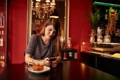 Νέα γυναικεία συνεδρίαση χαμόγελου σε έναν φραγμό Στοκ φωτογραφία με δικαίωμα ελεύθερης χρήσης