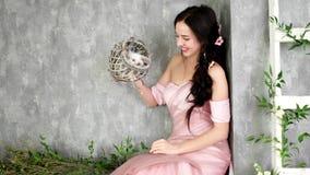 Νέα γυναικεία τοποθέτηση στο στούντιο φωτογραφιών που κρατά το μικρό άσπρο κουνέλι στο ψάθινο γκρίζο καλάθι, κορίτσι που έχει τη  απόθεμα βίντεο