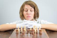 Νέα γυναικών νοσοκόμων κομμάτια παιχνιδιών σκέψης ματ σκακιού γιατρών παίζοντας Στοκ Εικόνες
