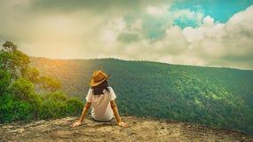 Νέα διακινούμενη γυναίκα που φορά το καπέλο και που κάθεται στην κορυφή του απότομου βράχου βουνών με τη χαλάρωση της διάθεσης Ασ στοκ εικόνες