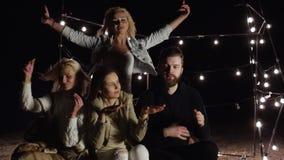 Νέα διασκέδαση φίλων που χορεύει στην παραλία στη νύχτα στο υπόβαθρο του ντεκόρ με τους λαμπτήρες απόθεμα βίντεο